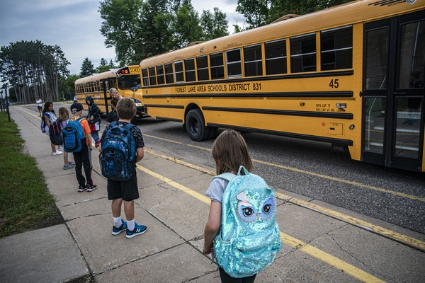 Children arrive for classes at Forest View Elementary where social distancing is enforced.