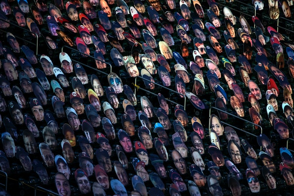 Carboard cutouts of fan faces in the stands of Target Field