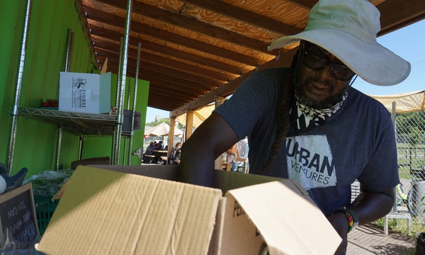 Gary Ross stocked vegetables at a free stand near the Midtown Greenway. Help is emerging for farmers that supply local markets.