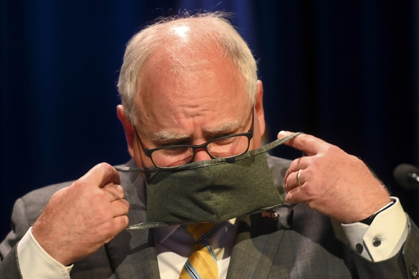 Minnesota Gov. Tim Walz put his face mask at the conclusion of a press conference in July 2020.