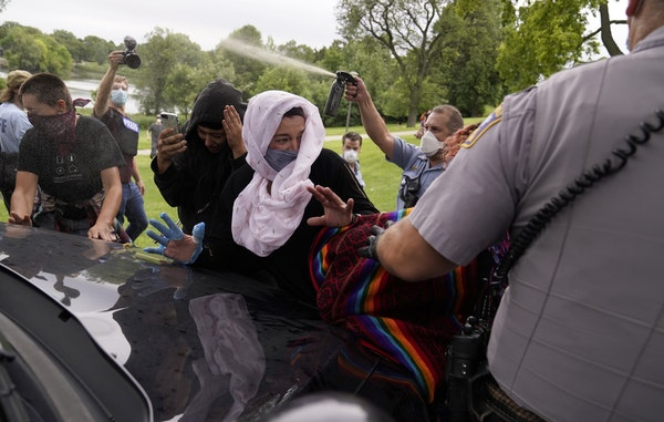A Minneapolis park police officer sprayed mace after protesters blocked the path of a cruiser attempting to leave the area in Powderhorn Park on Frida