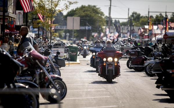 People ride through downtown Sturgis, S.D., during the 80th annual Sturgis Motorcycle Rally on Monday, Aug. 10, 2020.