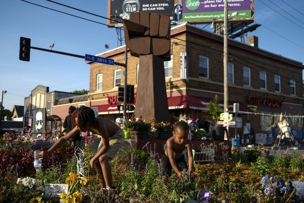Mister Smith, 7, and his little brother, Sir'Miles Smith, 4, watered the plants at the memorial in the 38th Street and Chicago Avenue intersection n