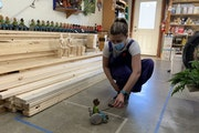 Miranda Gray-Burlingame test-drives one of the newest handmade wooden toys at Lark Toys in Kellogg, Minn. Her family-owned shop is one of many Minneso