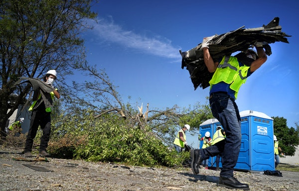 Neighbors, volunteers and contract workers in Cedar Rapids cleaned up debris from the derecho that ripped through Iowa on Aug. 10.