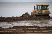 A bulldozer pushed dirt along Park Point beach as part of an effort to raise the beach front and protect homes.