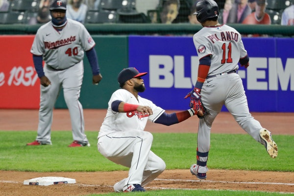 Cleveland's Carlos Santana, center, tags out the Twins' Jorge Polanco, right, at first base in the seventh inning
