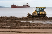 The Mesabi Miner pulled into Duluth Harbor on Tuesday as a bulldozer pushed dirt along Park Point as part of an effort to raise the beachfront.