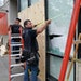 Seth Johnson, a supervisor with MP Johnson Construction, measured a window to be boarded up at Brit's Pub on Nicollet Mall.