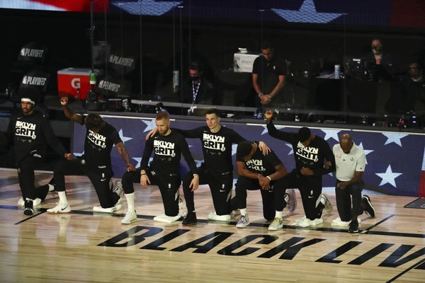 Brooklyn Nets players kneel for the national anthem before of Game 4 of an NBA basketball first-round playoff series, Sunday, Aug. 23, 2020, in Lake B