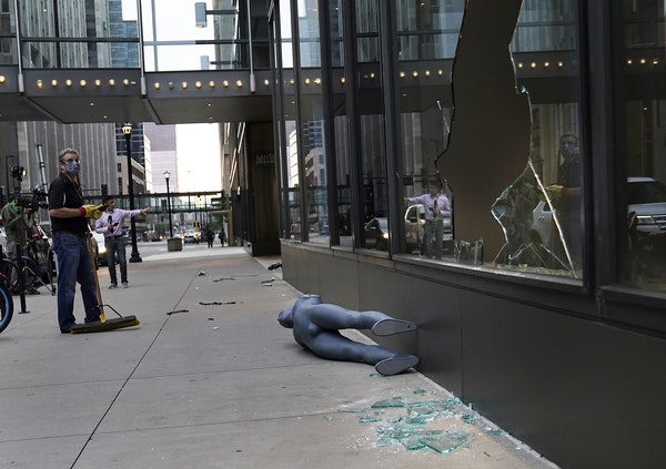 Tom Stellar, a pastor at Bethlehem Baptist Church, looked up at broken windows while cleaning up damage outside Nordstrom Rack at the IDS Center in Mi