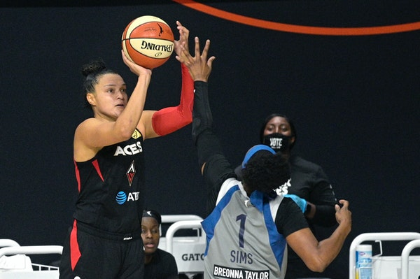 Las Vegas guard Kayla McBride goes up to shoot in front of Lynx guard Odyssey Sims