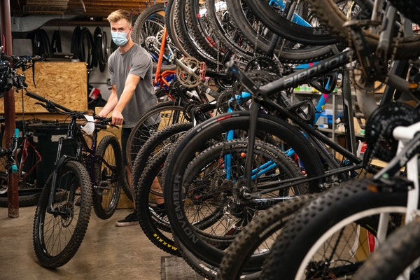 Braeden Cox, a service technician at Ski Hut, rolled out a finished bike to return to a customer on Thursday. As with other retailers in the outdoors,