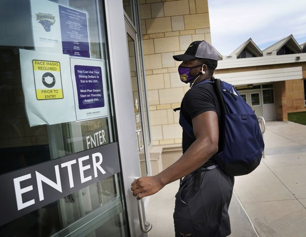 Students moved last month into dormitories at Minnesota State University Mankato, where signs on campus reminded students to wear masks to fight the c