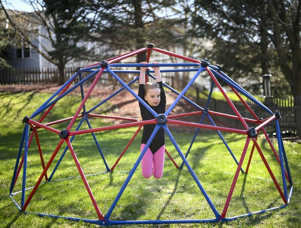 """Eloise Gehring, 6, hung from her and her brother's backyard play set Wednesday in Woodbury. She says the pandemic makes her sad. """"I just miss going to"""