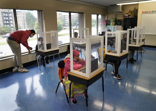 It was back to school for some students at Harvest Best Academy Tuesday in Minneapolis, but with masks, plastic barriers and other new precautions in