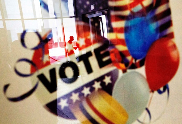 In this Nov. 1, 2016, photo, a voter is reflected in the glass frame of a poster while leaving a polling site in Atlanta, during early voting ahead of