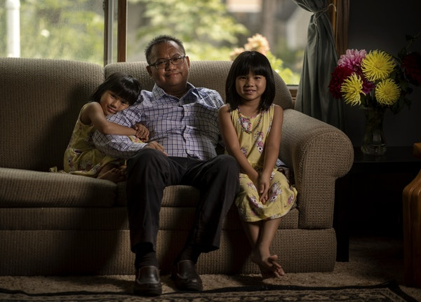 """""""It was a very tough thing to take in,"""" said Dr. Nyan Pyae, seen in his Roseville home with his twins, May Hninpwint, left, and Mya Moesett. """"I"""
