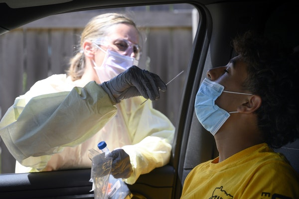 North Memorial RN Andrea Driskill administered a COVID-19 test to Dominick Brown, 15, in July behind the North Memorial Speciality Center in Robbinsda