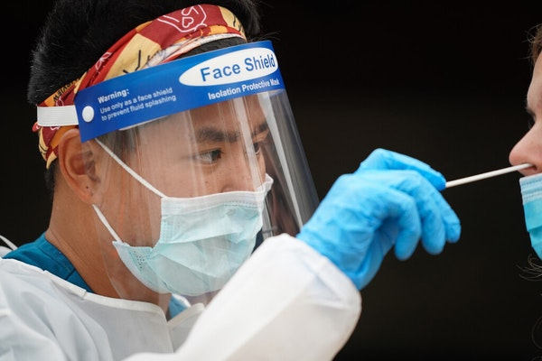 Photo by Shari Gross:Hien Bui, an EMT with M Health Fairview and registered nurse, administered a COVID-19 test during a free testing event at New Sal