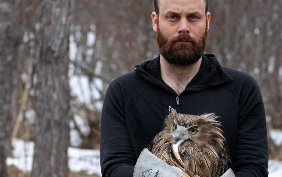 Author Jonathan C. Slaght and one of the female fish owls he caught and tracked in Russia.