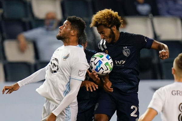 Minnesota United defender James Musa, left, heads the ball against Sporting Kansas City forward Gianluca Busio