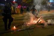 Minneapolis Police officers worked to extinguish a fire outside the Hennepin County Jail Thursday night.