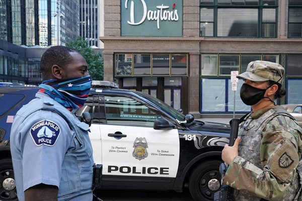 A Minneapolis police officer talked with a member of the Minnesota National Guard in downtown Minneapolis after a night of looting in August.