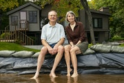 Cheryl and Bob Koll posed on their sandbag wall in Lake Shamineau in front of their home of 50 years, which they are fighting to save.