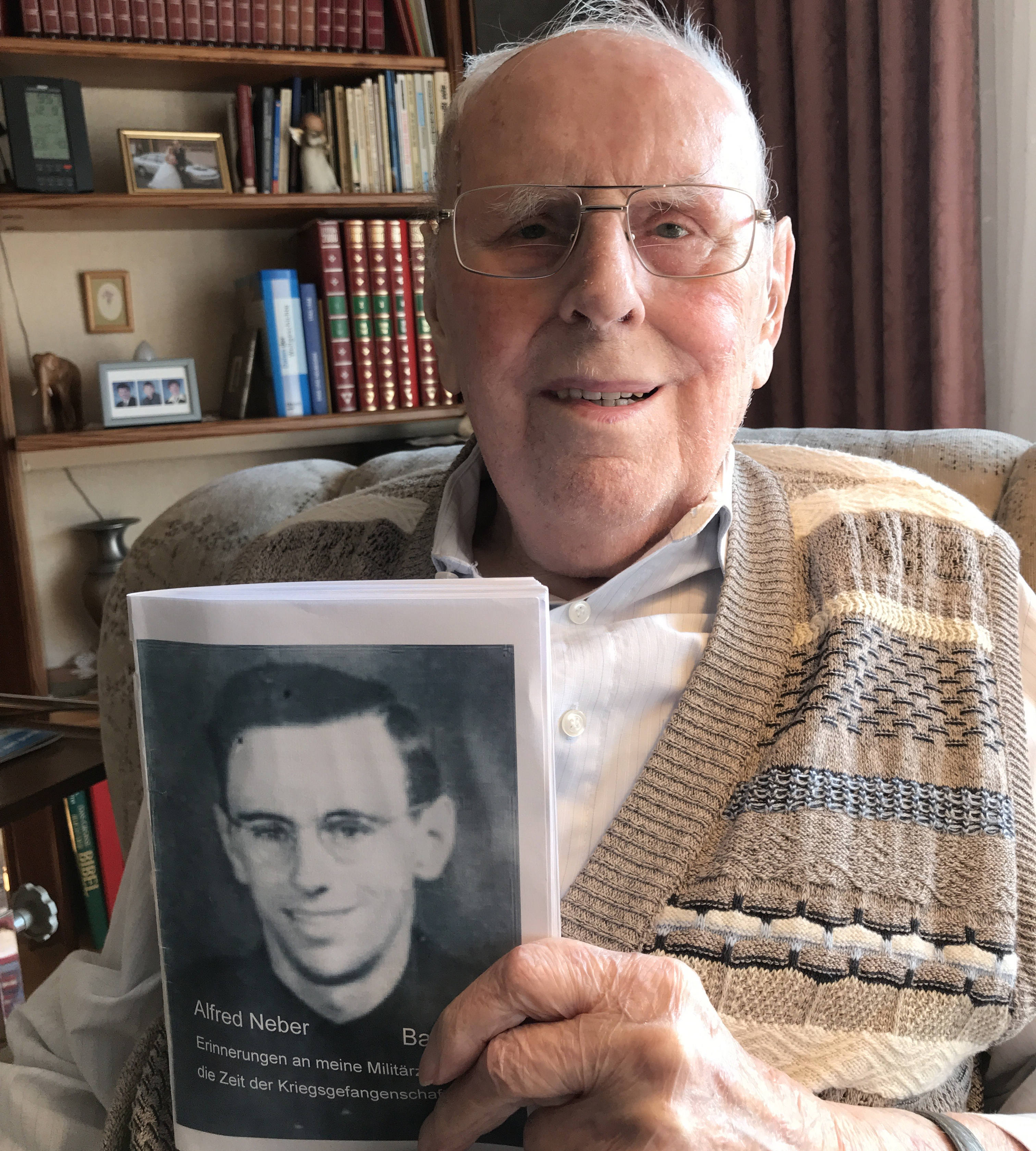 Alfred Neber, 95, who lives in Germany near Heidelberg, holds a photo of himself taken when he was about 20, around the time he was sent to work in Minnesota as a POW.