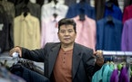 Long Her, a Hmong refugee, voted for Hillary Clinton in 2016, but now he's considering voting for Trump after his business, New Fashions Tailoring & A