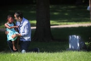 During a visit to Emily Hofher's grave site, Hofher's husband Rob Raub and their daughter Ruby Raub, 4, share a quiet moment together in July in M