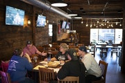 Daniel Hull, second from left, met with his managers at the Nutty Squirrel Sports Saloon on Wednesday to discuss how they would adapt to Wisconsin's n