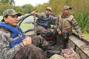 Trevor Montez, center, steered his mud boat through a backwater on the Mississippi River on his family's return from the state duck season opener no