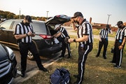 A parking lot gave game officials (left to right) Jason Vogt, Andrew Aller, Brian Grandstand, Dan Sigl and David Rivera distance to gear up for Friday