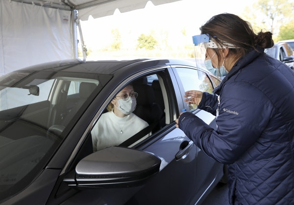 Nursing assistant Monica Brodsky, right, handed McKensie Burreson, of Madison, Wis., a funnel and vial for a saliva test for COVID-19 at a drive-throu