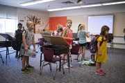 Second-grade kids stood with their belongings before joining other in-school day-care kids for supervision by YMCA staffers at Rosemount Elementary Sc
