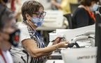An election worker scans a ballot while doing the first check of the signature while processing ballots at the Pima County Elections Office located in