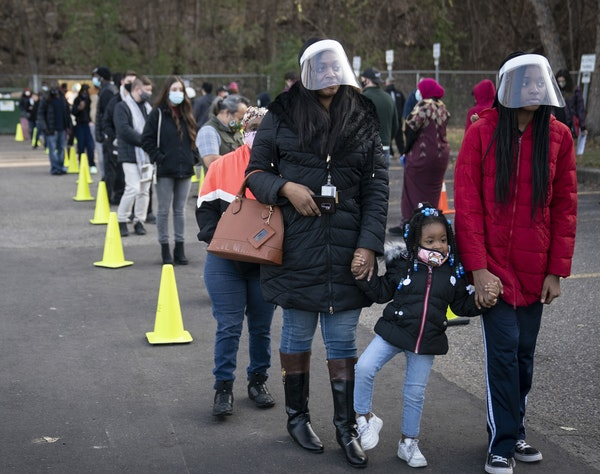 Natasha DaVis and her daughters Natavia DaVis and Natasia DaVis waited in a long line at the Ramsey County Elections office in St. Paul on Monday, Nov