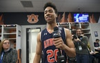 Auburn forward Myles Parker holds a media microphone during media availability in the team locker room.