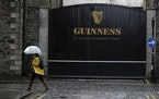 A woman passes the Guinness brewery in Dublin's city centre Wednesday Nov. 11, 2020.