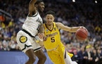 Minnesota's Amir Coffey (5) drives past Michigan State's Aaron Henry (11) during the first half.