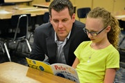 Bremer Bank's Mike Yanisch helps out students like Ava Matza at Liberty Ridge Elementary in Woodbury.
