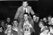 George Mikan (99) hoisted coach John Kundla after the Lakers won their third NBA title in four seasons in 1952.
