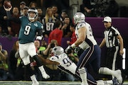 Philadelphia Eagles quarterback Nick Foles (9) got a pass away under pressure from New England Patriots defenders Trey Flowers (98) and Lawrence Guy (