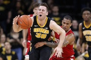 Iowa guard Connor McCaffery is fouled by Indiana guard Devonte Green, right, during the second half of an NCAA college basketball game Friday, Feb. 22