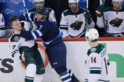 Winnipeg Jets' Ben Chiarot (7) and Minnesota Wild's Nick Seeler (36) mixed it up during the third period of Game 2.