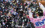 Second-place Racing Point driver Sergio Perez of Mexico, right, poured champagne on winner Mercedes driver Lewis Hamilton of Britain on the podium of