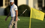 Dustin Johnson looks over his shot on the 18th green during the third round of the Masters