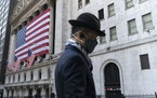 A man wearing a mask passes the New York Stock Exchange, Nov. 16, 2020, in New York.